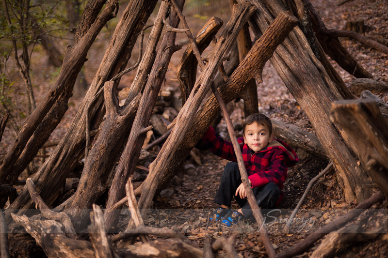 Pre-school boy in a wooden teepee wearing buffalo plaid during a Houston Metro Outdoor Family session in the woods